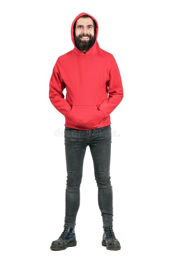 Punker farpado de riso que veste o hoodie vermelho que olha a câmera com mãos em uns bolsos fotografia de stock royalty free