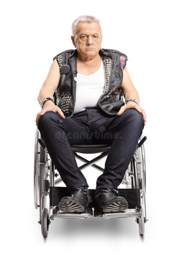 Punker masculino maduro serio en una silla de ruedas imagenes de archivo