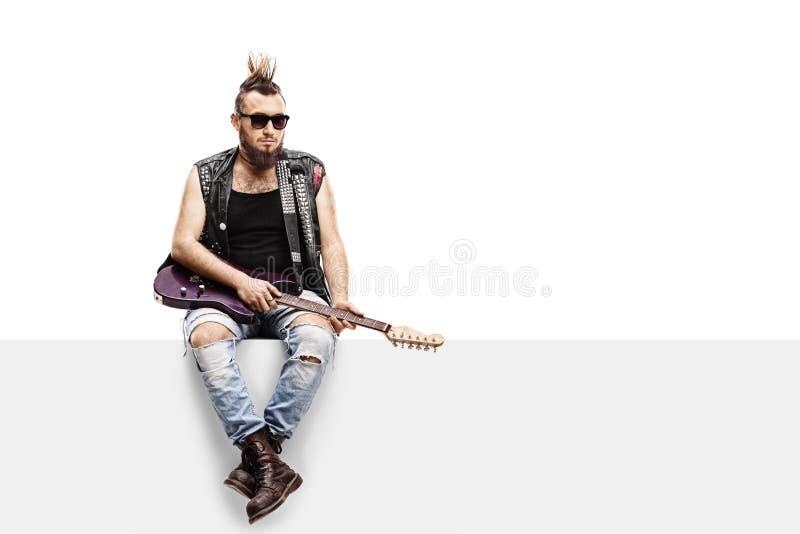 Punker novo com uma guitarra elétrica que senta-se em um painel foto de stock royalty free