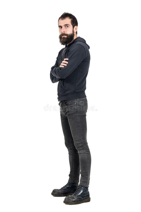 Punker sérieux sûr utilisant de vieilles bottes portées et pull molletonné à capuchon noir regardant l'appareil-photo photographie stock