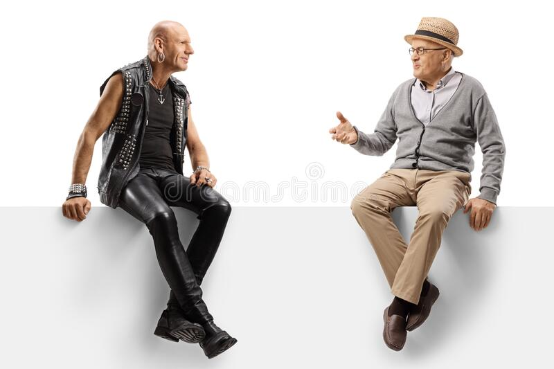 Punker talking to an elderly manand sitting on a panel stock image