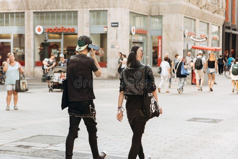 Punkies o amigos jovenes de los pares que caminan abajo de la calle en Leipzig fotos de archivo