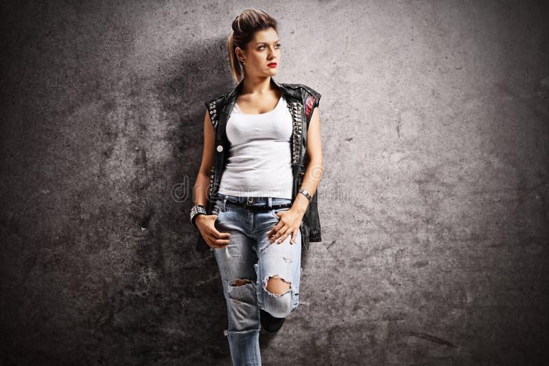 Punkmädchen, das an einer rostigen grauen Wand sich lehnt stockfotografie