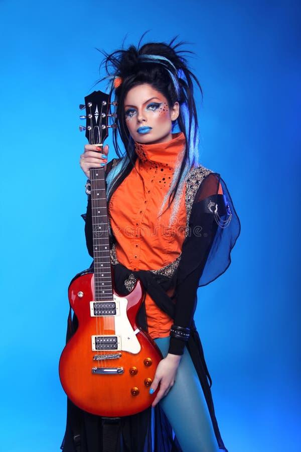 Punkmädchengitarrist, der über blauem Studiohintergrund aufwirft Modisches r stockbilder