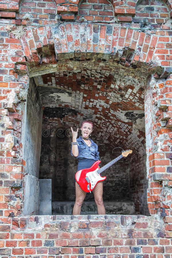 Punkowa dziewczyna z gitary elektrycznej pozycją w okno zdjęcia royalty free