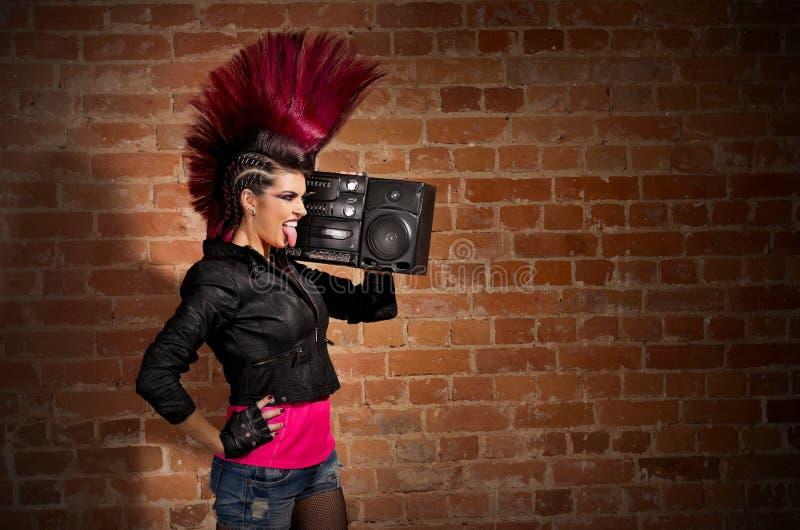 Punkrockflicka på bakgrund för tegelstenvägg arkivbilder