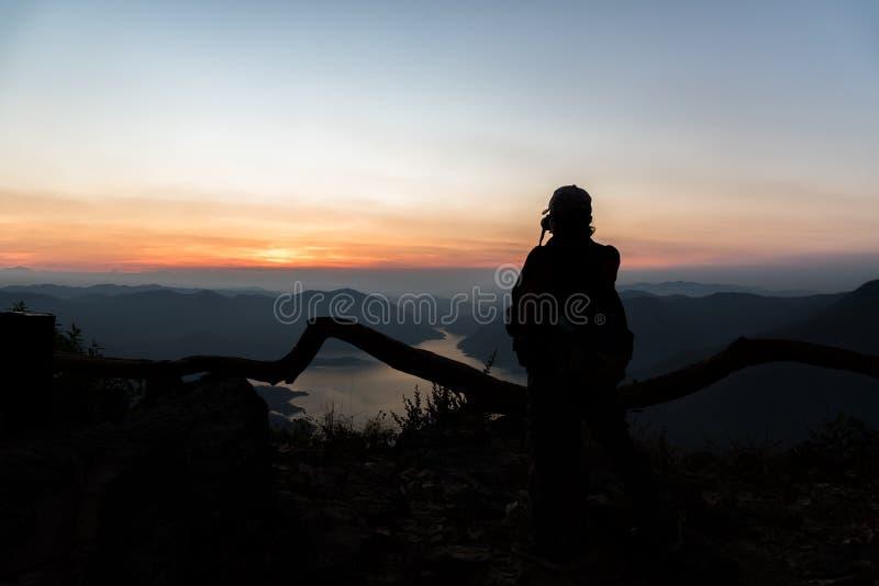 Punkt för Mae Ping flodsikt Konturkvinnaanseende och sesjö och berg på soluppgång arkivfoton