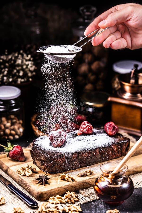Punkt w czekoladowym syropie z truskawkami Okurzanie sproszkowany cukier od durszlaka obrazy stock