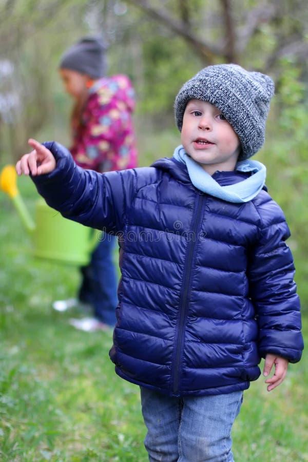 Punkter för en trädgård för pojke på våren hans finger till sidan Barn i trädgården i vår arkivbilder