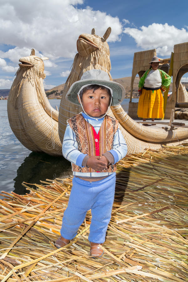 Puno, Peru - circa June 2015: Small boy in traditional clothes and canoe boat at Uros floating island and village on Lake Titicaca royalty free stock image