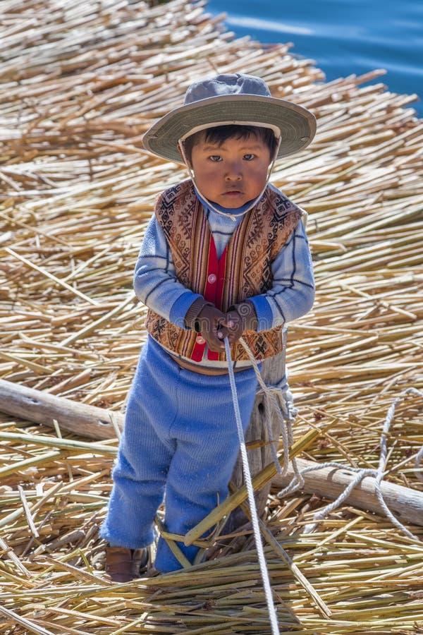 Puno Peru - circa Juni 2015: Liten pojke i traditionell kläder på Uros som svävar ön och byn på sjön Titicaca nära Puno, Pe royaltyfria bilder