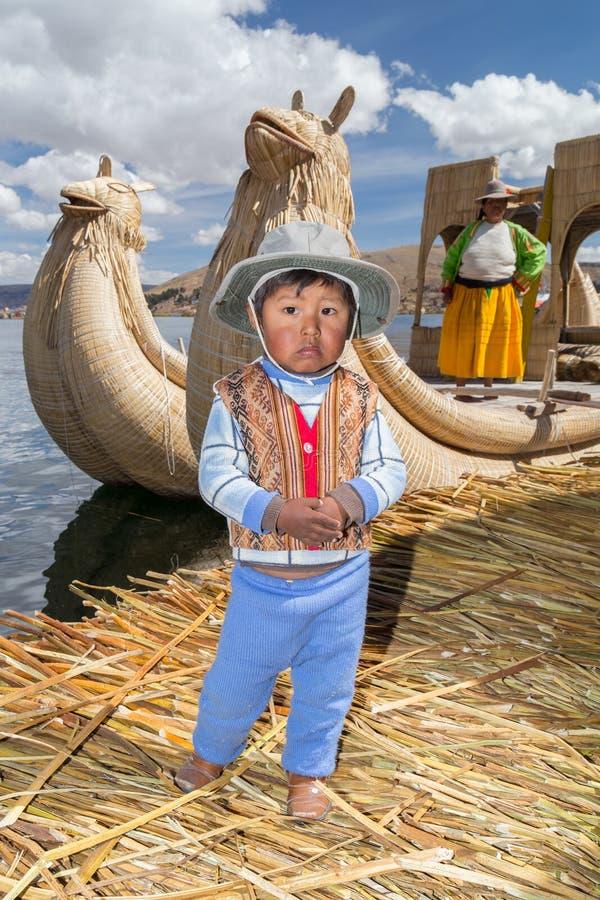 Puno Peru - circa Juni 2015: Liten pojke i traditionellt kläder och kanotfartyg på Uros som svävar ön och byn på sjön Titicaca royaltyfri bild