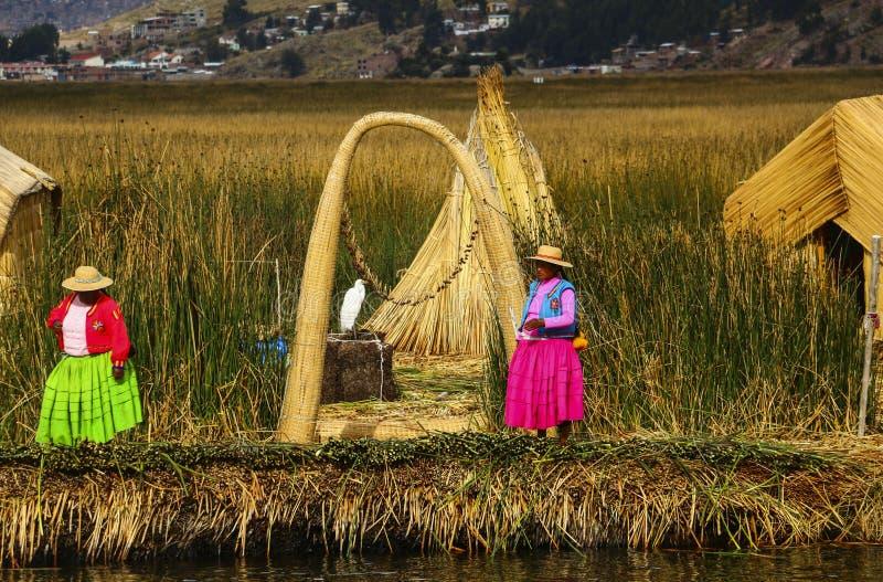 PUNO PERU - NOVEMBER 11, 2015: Kvinnor i traditionella dresser på Uros Islands, sjö Titicaca, Peru royaltyfria foton