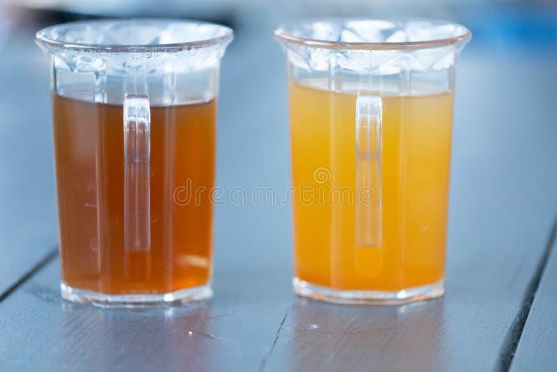 Punsch ou gluhwein colorido do perfurador do Natal em uns copos plásticos foto de stock
