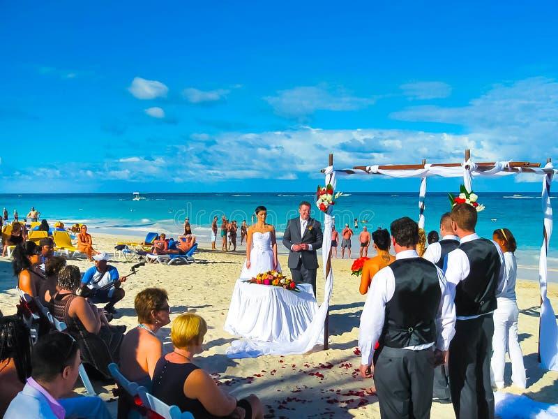 Punta Cana, Dominikanische Republik - 2. Februar 2013: Bräutigam und Braut, die am Strand stehen stockfoto