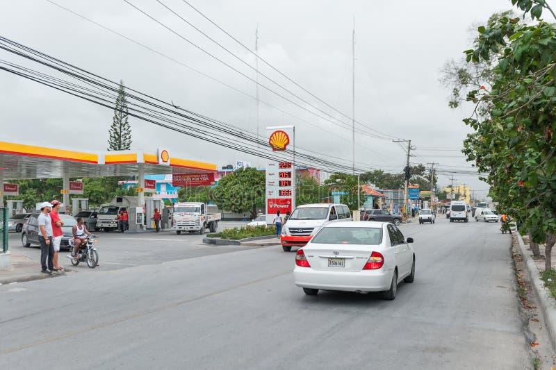PUNTA CANA, republika dominikańska - CZERWIEC 18, 2015: Republiki Dominikańskiej ulica z lokalnymi ludźmi i ruchem drogowym Shell obrazy royalty free