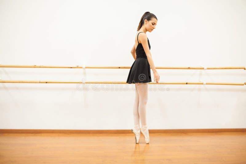Punta del ballerino di balletto che pianta accanto ad una sbarra fotografie stock