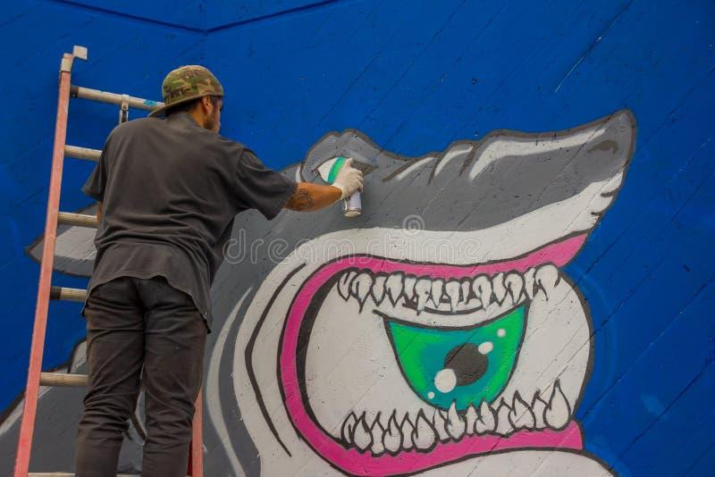PUNTA DEL ESTE, УРУГВАЙ - 6-ОЕ МАЯ 2016: молодой человек стоя в лестнице заканчивая граффити иллюстрация вектора