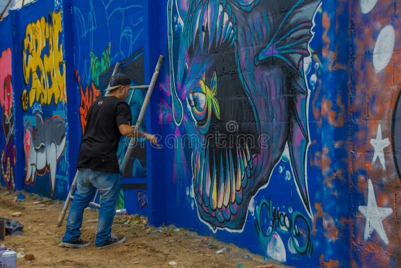 PUNTA DEL ESTE, УРУГВАЙ - 6-ОЕ МАЯ 2016: неопознанные люди с щеткой на руке крася некоторые детали на граффити бесплатная иллюстрация