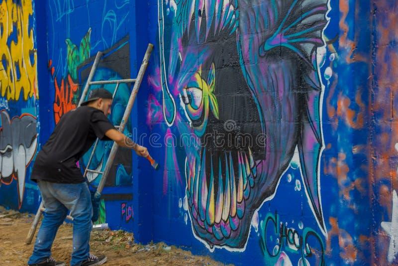 PUNTA DEL ESTE, URUGUAY - 6 MAI 2016 : jeunes hommes non identifiés avec une brosse sur sa main peignant un graffiti image libre de droits