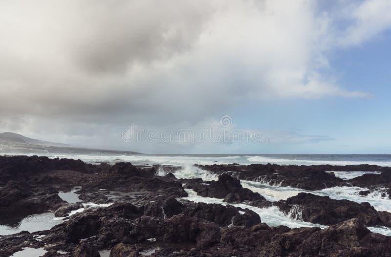 Punta del Hidalgo, Tenerife, Espania - Oktober 27, 2018: Panorama van het rotsachtige strand van Punta DE Hidalgo en de golven di royalty-vrije stock foto
