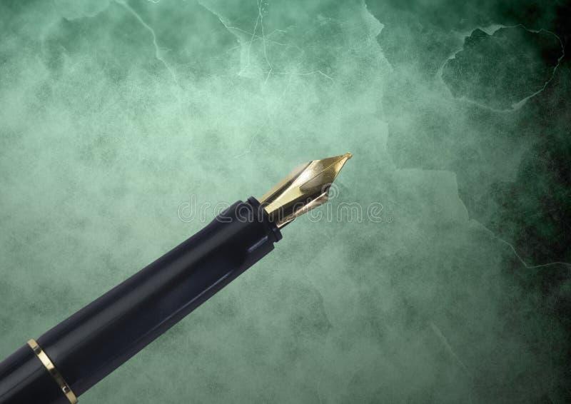 Punta dell'oro della penna stilografica contro fondo classico verde fotografia stock