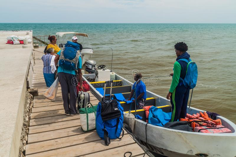 PUNTA GORDA, BELIZE - 9 DE MARÇO DE 2016: Passageiros que embarcam um barco à Guatemala de Livingston em um porto da cidade de Pu foto de stock