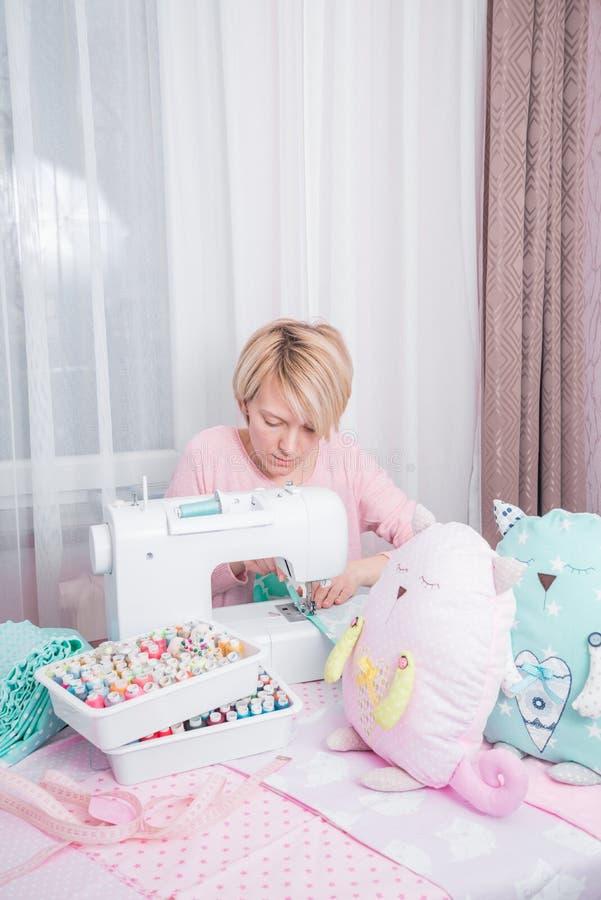 Puntada de la mujer en casa en la máquina de coser fotografía de archivo libre de regalías