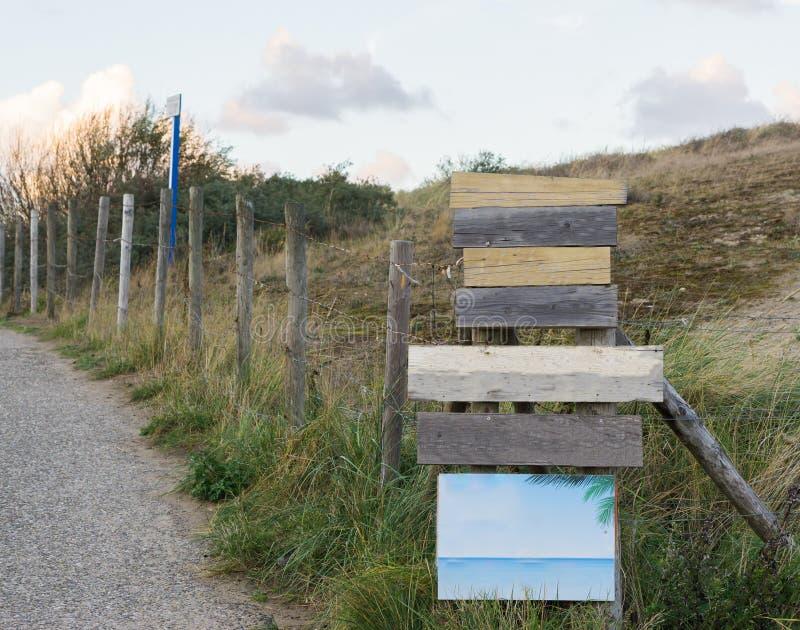 Puntatori di legno di modo e bordi in bianco vuoti del segno per mettere il vostro testo dentro con erba verde un recinto e una s fotografie stock libere da diritti
