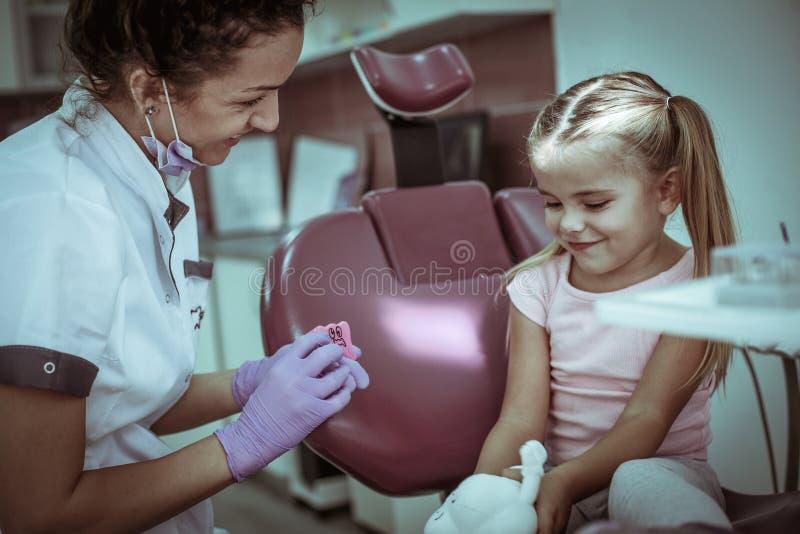 Punte d'ascolto del dentista della bambina fotografia stock libera da diritti
