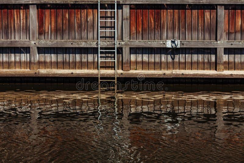 Puntelli il canale con le scale e la riflessione in acqua sul fiume del danese in Klaipeda, Lituania fotografia stock