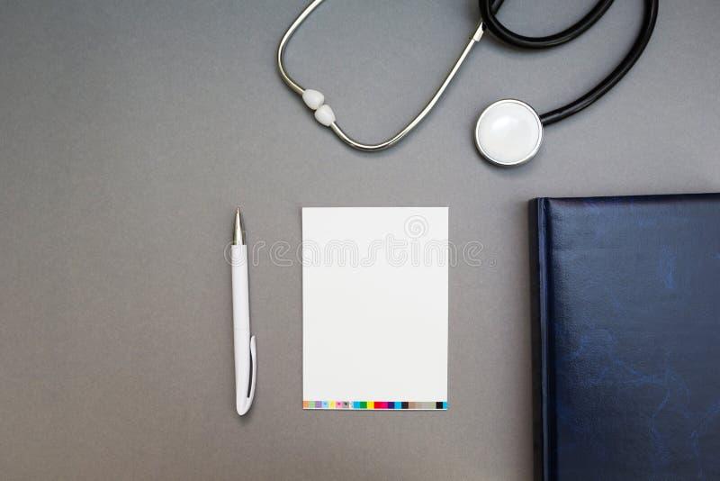 Punten, een stethoscoop en een notitieboekje op een grijze achtergrond, de werkende plaats van de arts royalty-vrije stock foto