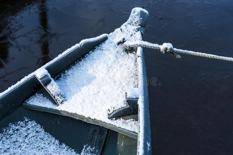 Punter Boat in Winter. Part of green punter boat in winter with snow and rope and ice on the water royalty free stock photo