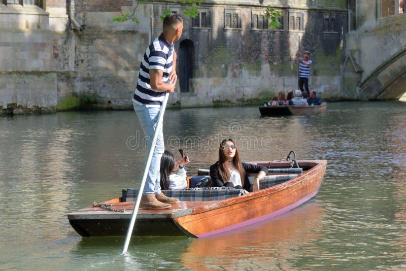 Punter guiding asian tourists on Cam Cambridge England. Cambridge England, United Kingdom -May 20, 2016: Punter guiding asian tourists on Cam Cambridge England stock photos