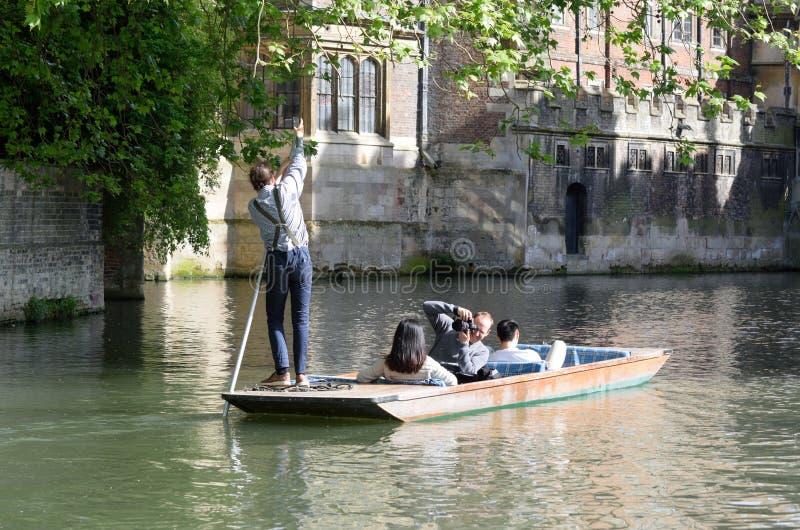 Punter guiding boat of tourists on Cam Cambridge England. Cambridge England, United Kingdom -May 20, 2016: Punter guiding boat of tourists on Cam Cambridge stock photography