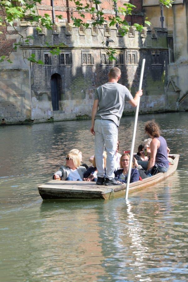 Punter guiding tourist on Cam Cambridge England. Cambridge England, United Kingdom -May 20, 2016: Punter guiding tourist on Cam Cambridge England stock images