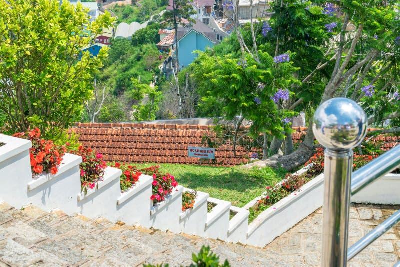 Punti con i fiori sull'inferriata e gli alberi tropicali nel parco fotografia stock libera da diritti