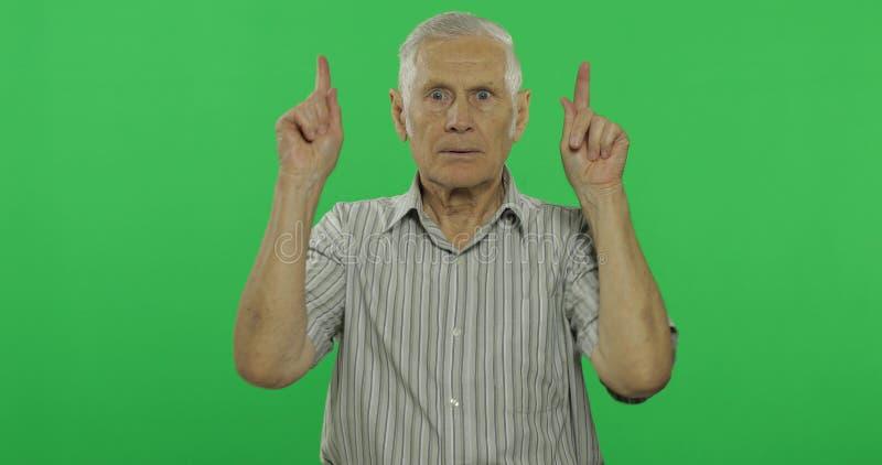 Punti dell'uomo senior alla cima Uomo anziano bello sul fondo chiave di intensità immagini stock