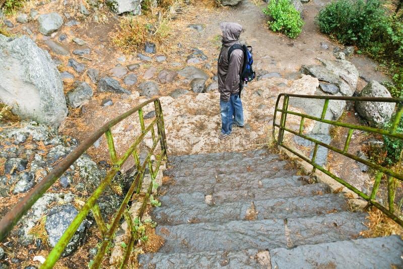 Punti di pietra e turista in pioggia fotografie stock