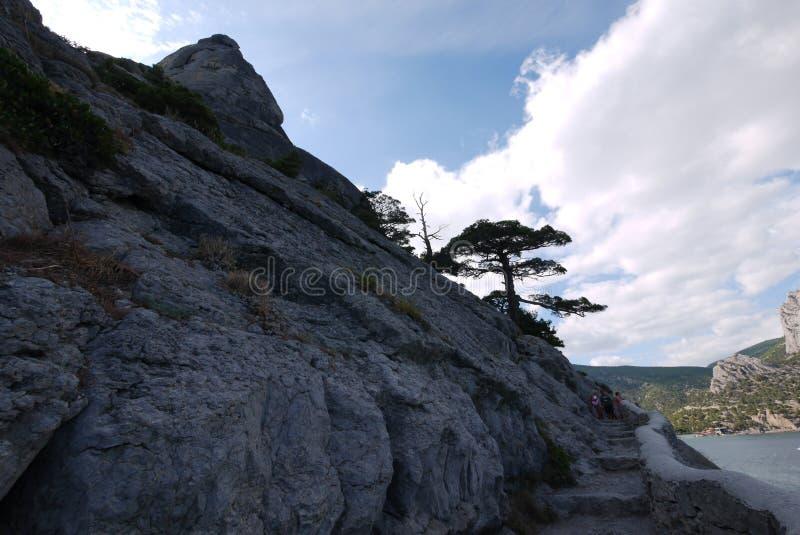 Punti di pietra, scavati fuori in una montagna rocciosa contro un mare blu e un cielo nuvoloso immagini stock