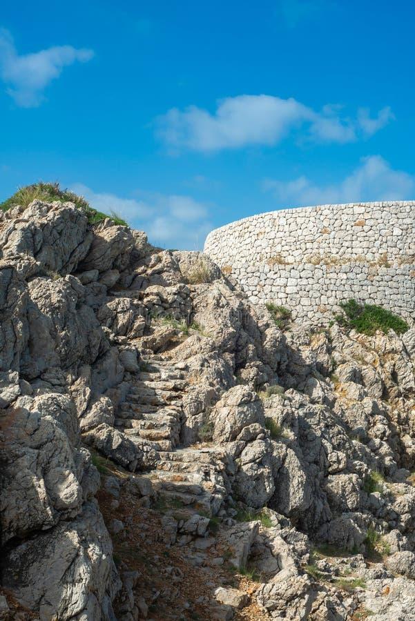 Punti di pietra vecchi di sbriciolatura e parete di pietra con cielo blu, Mallorca, Spagna immagine stock