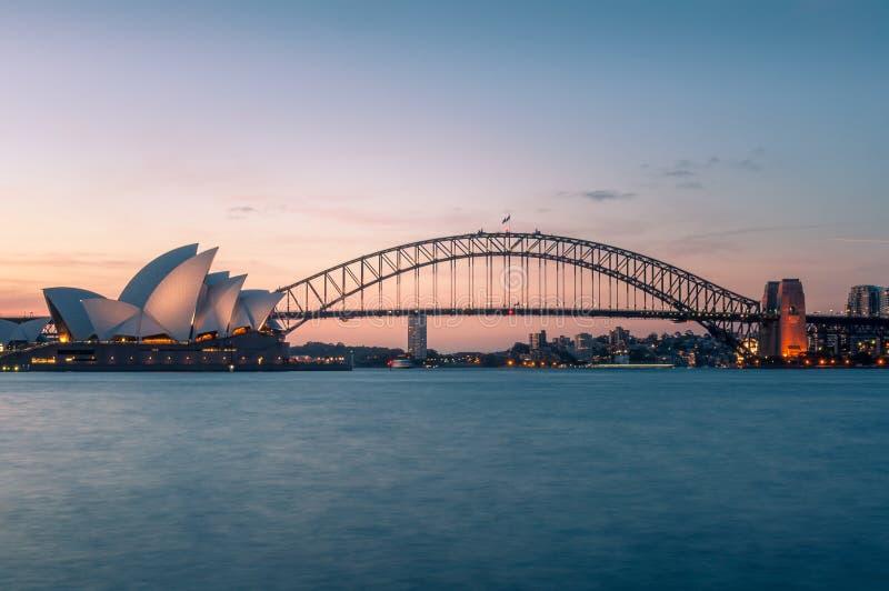 Punti di riferimento iconici di Sydney di Sydney Opera House e di Sydney Harbour Bridge al crepuscolo fotografia stock libera da diritti