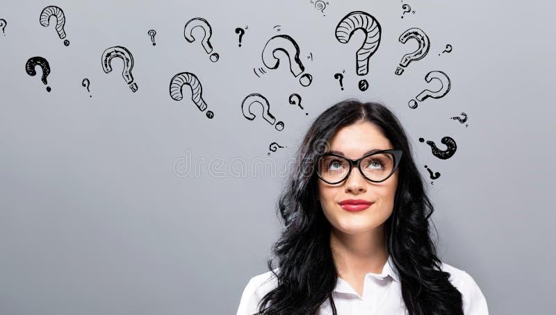 Punti interrogativi con la giovane donna di affari immagini stock