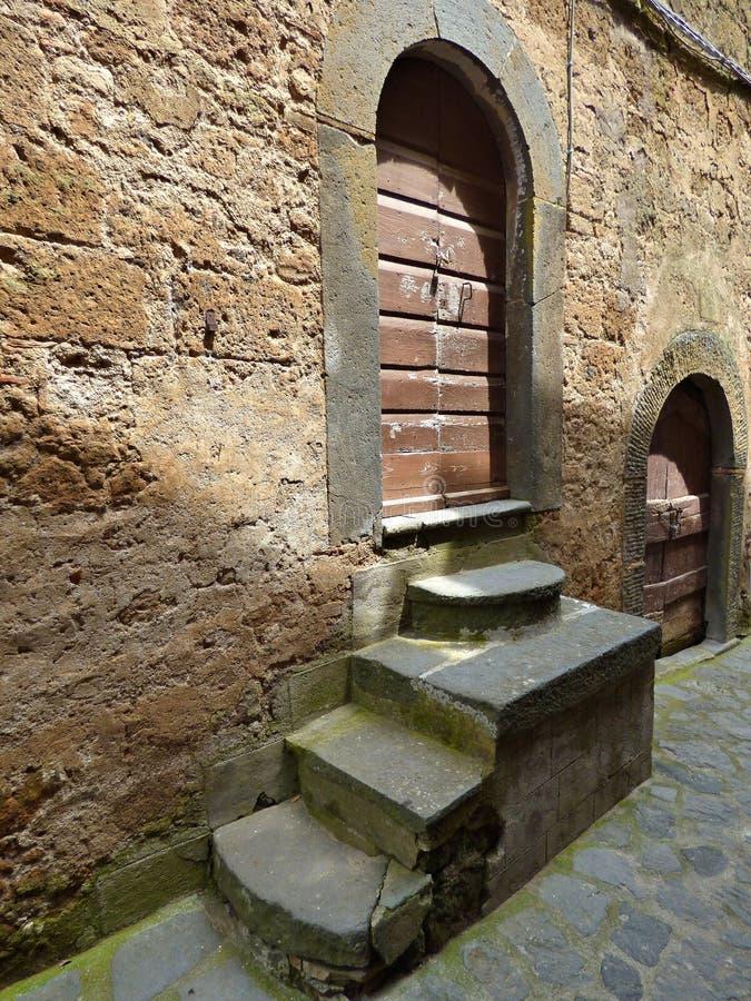 Punti medievali che conducono alla porta di legno stagionata di una casa immagini stock
