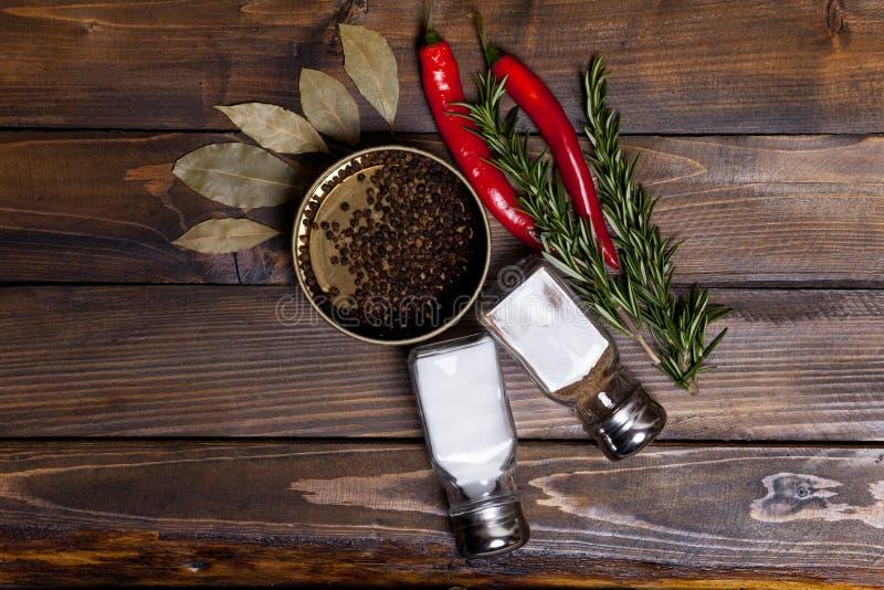 Puntillas de la pimienta y del romero de chile rojo con las hojas del laurel y los guisantes negros de la pimienta en un tarro, l imágenes de archivo libres de regalías