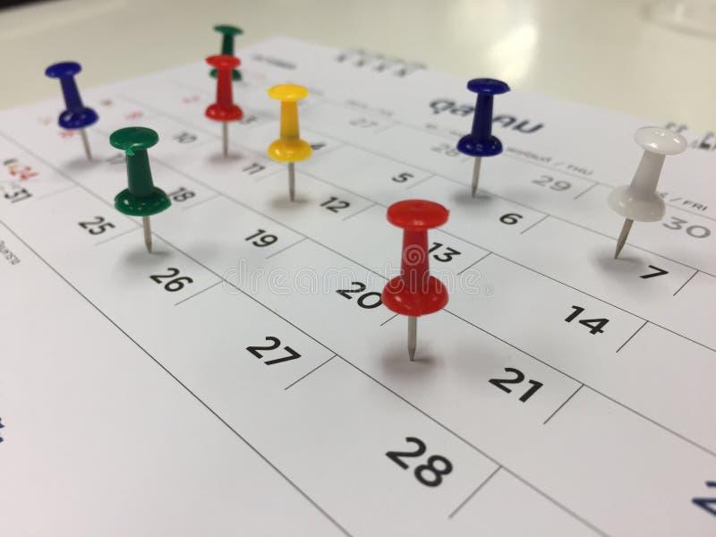 Puntina da disegno nel concetto del calendario per occupato, ricordo di riunione e di appuntamento immagine stock