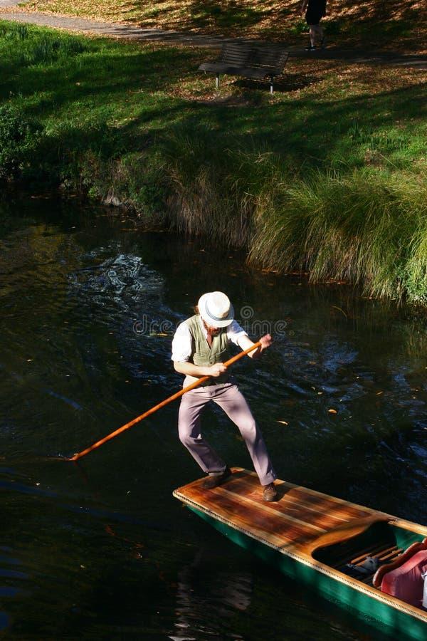 punting Биржевой игрок в одеждах Edwardian и белой шляпе стимулируя деревянную плоскодонную шлюпку отдыха в мелководье стоковое фото