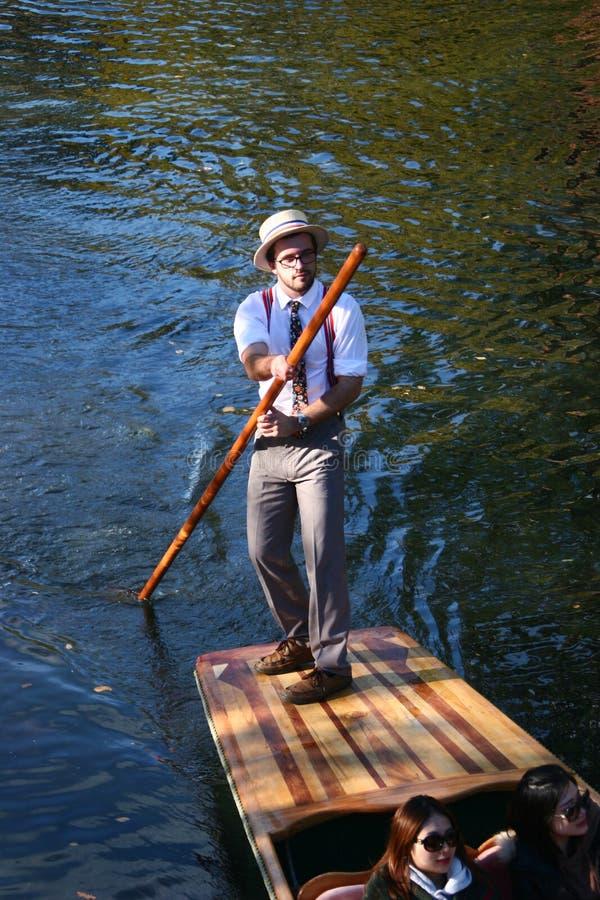 punting Биржевой игрок в одеждах Edwardian и белой шляпе стимулируя деревянную плоскодонную шлюпку отдыха в мелководье стоковое изображение