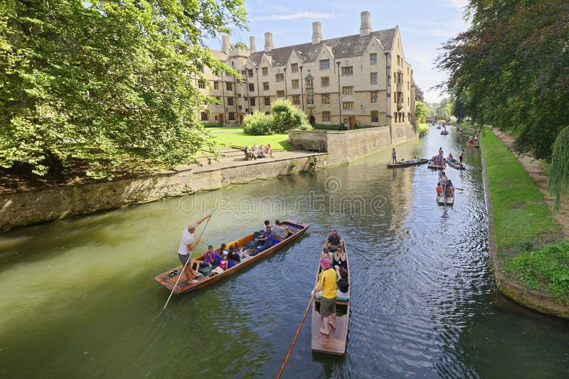 Punting canals Cambridge England. tourists. Punting boats full of people being pushed down one of Cambridge`s canals by punters with punting poles on a beautiful royalty free stock photography
