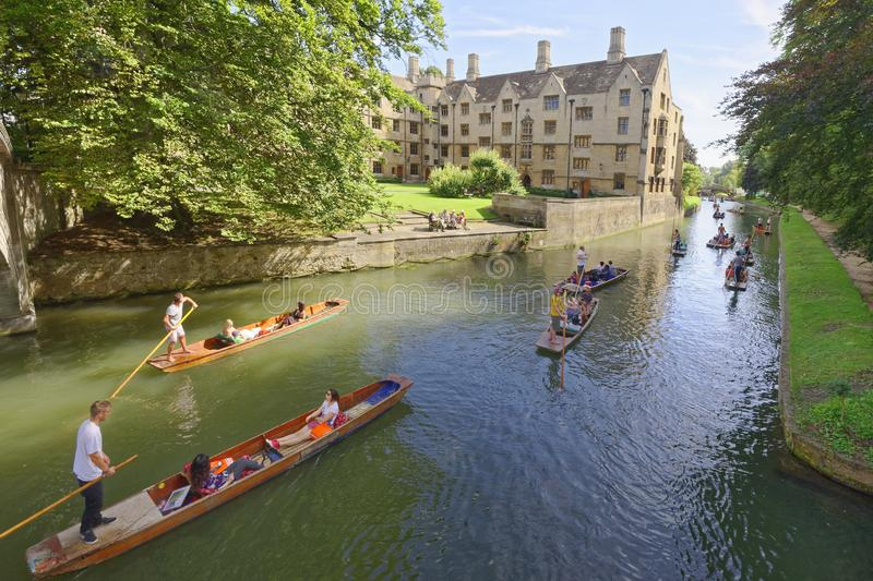 Punting canals Cambridge England. tourists. Punting boats full of people being pushed down one of Cambridge`s canals by punters with punting poles on a beautiful royalty free stock photos